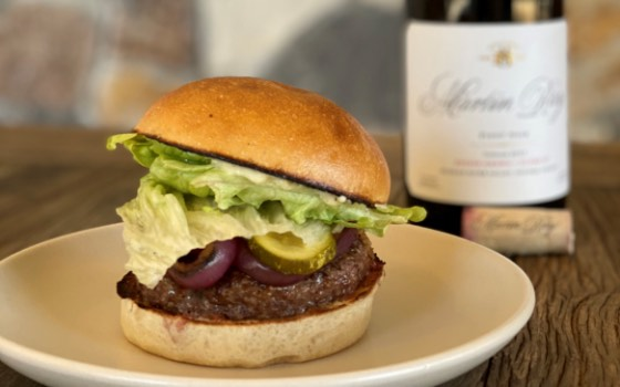 Hamburger on plate with Martin Ray wine bottle in background